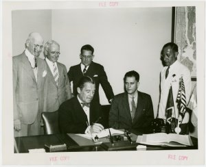 Nicaragua Participation - Noel Ernesto Pallais (Consul General) and Grover Whalen sign contract as group looks on