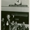 """Opening Day - 1940 Season - Woman holding """"""""Hello Folks"""""""" labels in front of Waltham Watches sign"""