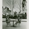 Sports - Ice Skating - Man on ice skates jumping over two chorus girls sitting at table