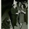 Ticket Sales - Fred Allen selling ticket books to woman and two men while other man lights match from his shoe
