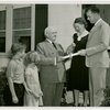 Typical American Family - Cramer family receiving key and lease from Harvey Gibson