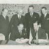 Grover Whalen signing contract with official for Uruguay participation while others look on