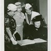 Women's Groups - Anna Neagle signing guestbook while Anna Kross, Bertha McCann and Dorothy Frooks looks on