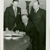 Yugoslavia Participation - Constantin Fotich (Ambassador) signing guestbook while Julius Holmes and Edward Roosevelt look on