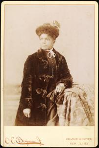 [Studio portrait of woman wearing hat, and velvet coat.]
