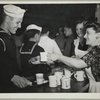 Bea Lille handing out coffee to a sailor