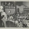 An audience of service men and hostesses watching George Jessel and an unidentified woman on stage.