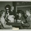 Mr. Cecil B. DeMille serving coffee to service men seated with hostesses