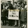 "Mixed race group of children carrying sign: ""No Child is Free Until ALL are Free,"" circa late 1950s"