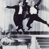 "The Nicholas Brothers wearing ""white tie and tails"" (full evening dress) leaping from a stage platform."