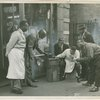 Harlem residents in front of shop listening to the radio, 1930s.