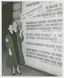 [Irma Sandre (Liat replacement) and William Tabbert (Lt. Joseph Cable) at theatre billboard for South Pacific]