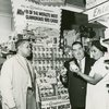 Mrs. Dottie V. Higgins, cashier; Mr. Ike Walton, manager; and Mr. Walter Seeman, sales representative of Carnation Milk Co. at Food Pageant located at 1727 Amsterdam Avenue during Carnation Milk Sweepstakes promotion