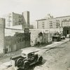 View of automobile parts and repair businesses on East 138th Street, looking towards Fifth Avenue, in Harlem, ca. 1944. Harlem Hospital is in center background. This site would later be cleared for the construction of the Riverton Houses.