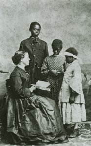 Portrait of teacher Laura M. Towne, a founder of the Penn School, with students Dick, Maria and Amoretta.