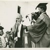 On the afternoon of his birthday, the University of Ghana conferred its first honorary degree on W.E.B. Du Bois. Here is Nana Nketsia IV, a paramount Chief who is Chairman of the University Council, placing the hood over Dr. Du Bois' head.