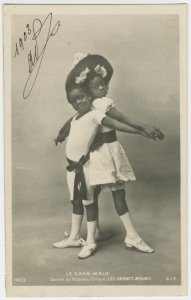"Le Cake-Walk.""Danse au Nouveau Cirque, LES ENFANTS NEGRES."" Photo postcard of young boy and girl in dance pose, back to back, clasping hands."