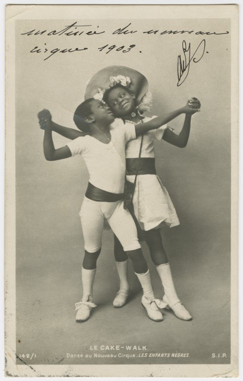 """Le Cake-Walk.""""Danse au Nouveau Cirque, LES ENFANTS NEGRES."""" Photo postcard of young boy and girl in dance pose, feet pointed and hands clasped, gazing at each other."""