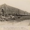 eneral view of construction train in rear hauling ties and rail. Seats in buckboard, John Grant, time keeper. Standing, Donald Grant, contractor, J.H. Benson, supt., Mr. Cox, paymaster, the camp doctor and a visiting Indian.
