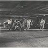 Jerome Robbins, crew, dancers: Underground parking garage: crew pulling cameramen on dolly, Robbins running along side dancers moving toward camera crew