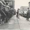 Jerome Robbins, crew, dancers: Exterior, city sidewalk: Jerome Robbins conducting warm-up class, row of male dancers in street clothes using basement railings for barre