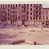 Exterior location: another rubble strewn lot, row of vacant tenements across the street in the background