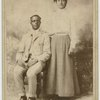 Studio portrait of a young couple, he seated, she with hand on his shoulder.]