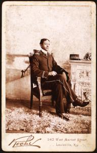 [Uniformed man seated, on the mantlepiece is his cap, embroidered with the name Miller Edison Phonograph Co.]