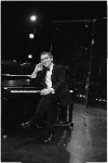 Joseph Papp sitting at piano with cigar in hand, December, 1986.