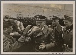 [The Fuhrer visited a Luftwaffe air base and sat near the Christmas tree in the midst of the troops.  He visited anti-aircraft positions in the Western Air Defense Zone, where a gunner presented him with a hand-carved wooden eagle.]