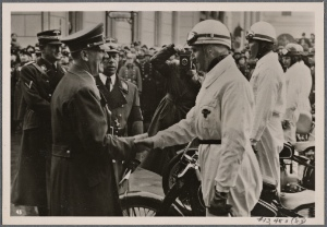 [The International Automobile show is opened by the Fuhrer.  He greets expert German drivers in front of the Reichs-chancellery.]