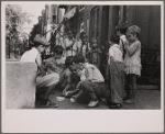 Children playing cards in front yard in slum area near Union Station. Section inhabited by both whites and Negroes. Washington, D.C.