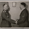 In his headquarters, the Führer personally awarded Colonel-General Rommel, commander of the German Afrika Korps, the Knight's Cross of the Iron Cross with Oak Leaves and Swords, making him only the sixth officer to receive it.]