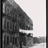 [Rear of tenements with debris in yard and hanging laundry: Manhattan]
