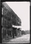 Rear of tenements with debris in yard and hanging laundry: Manhattan