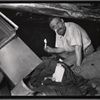[Man holding candle in basement surrounded by debris and rags: Manhattan]