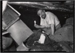 Man holding candle in basement surrounded by debris and rags: Manhattan