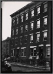 Residents posed at tenement windows and on stoop