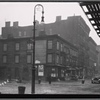 [Vacant wood frame tenement with storefronts; Bishop's crook lamp: 9th Ave. - W. 17th St., Manhattan]