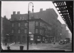 Vacant wood frame tenement with storefronts; Bishop's crook lamp: 9th Ave. - W. 17th St., Manhattan