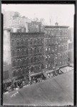 Tenements and storefronts with Christmas lights, from Elevated line: 1st Ave. - E. 12th St., Manhattan