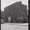 Vacant brick building; men loitering