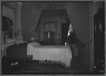 Railroad apartment interior view of bedroom with female resident