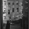 Inspector making notes in rear yard of vacant tenement