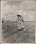 Mrs. Howard shows the beginning of a garden to a neighbor
