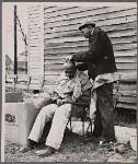 Negro getting a haircut in front of church which houses flood refugees. Sikeston, Missouri