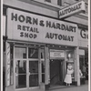 Horn and Hardart retail shop: exterior, woman posting sign -- everything automat