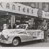 "125th Street Day Parade. View of automobile to carry ""Miss 125th Street"" during parade, sponsored by Kanter's Department Store depicted in background, Harlem, New York City, 1947"