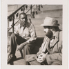 Artist Jacob Lawrence with film scholar and writer Jay Leyda, sitting on the steps of Lawrence's residence at 385 Decatur St., Brooklyn, New York, 1941.