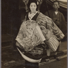Oiran parade participant in geta sandals accompanied by servant bearing parasol.